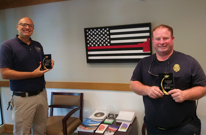 Two Firefighters Holding Awards