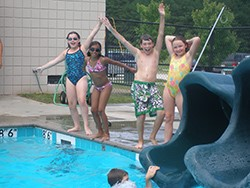 A group of kids plays at the edge of the pool